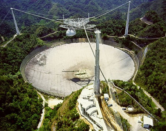 Large dish in the ground with 3 towers and cables leading to receiver above middle of dish.