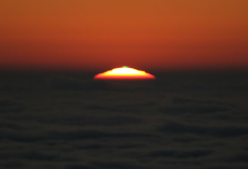 Sea of clouds, top of setting sun with tiny green spot on top against orange sunset sky.