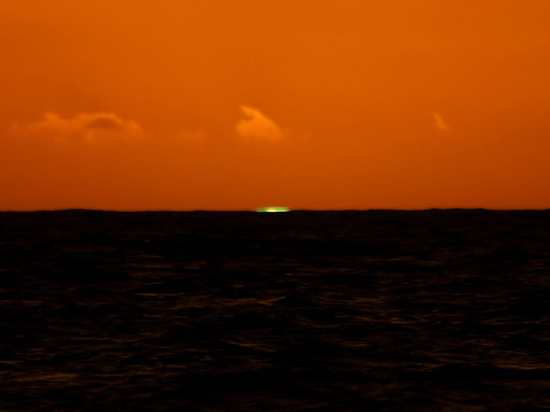 Orange sunset over dark ocean with small, wide green stripe right on horizon.