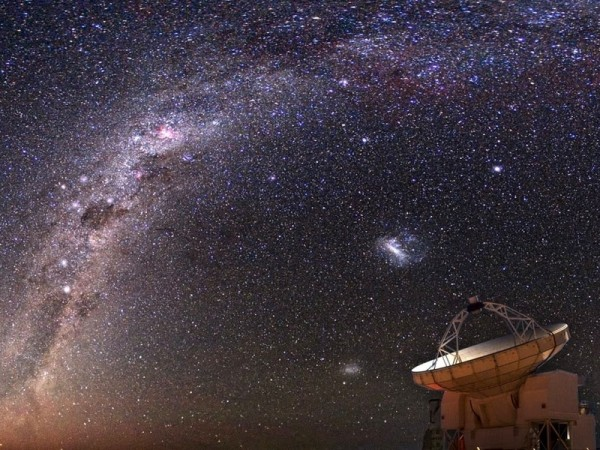 The sky over APEX: The image shows the southern region of the Milky Way with the stars Alpha and Beta Centauri, the Crux, and the region around Eta Carinae (bright reddish nebula above left of the image centre). The ATLASGAL survey with the APEX telescope covers the galactic plane up to the Carina region.   © © ESO/Y. Beletsky (sky photo) / ESO (APEX telescope) / image collation by C. Urquhart