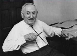 Smiling old man in white shirt sitting down, pointing at something.