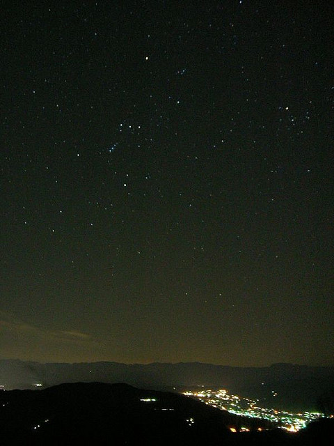 Constellation Orion over hilly landscape with city lights in foreground.
