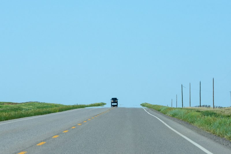 A classic highway mirage: the view forward, along a highway, with a car ahead appearing to be surrounded by water.