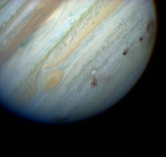 Brown spots mark the places where fragments of Comet Shoemaker-Levy 9 tore through Jupiter's atmosphere in July 1994.  Image and caption via Wikimedia Commons.
