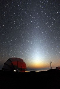 Zodiacal light against star field above red observatory dome.