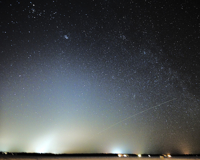 Lights along horizon, wide zodiacal light with star field above.
