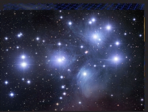 About a dozen very bright stars within swaths of blue misty stellar clouds.