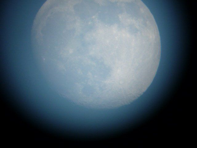 Closeup of large, white, nearly full gibbous moon against blue sky.