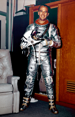Man wearing tight-fitting old style silver spacesuit and holding helmet.