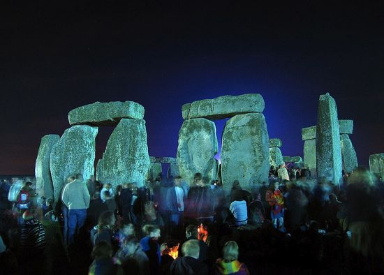 Night view of arches of huge rough-hewn vertical rocks with rocks lying across them. Crowd in foreground.