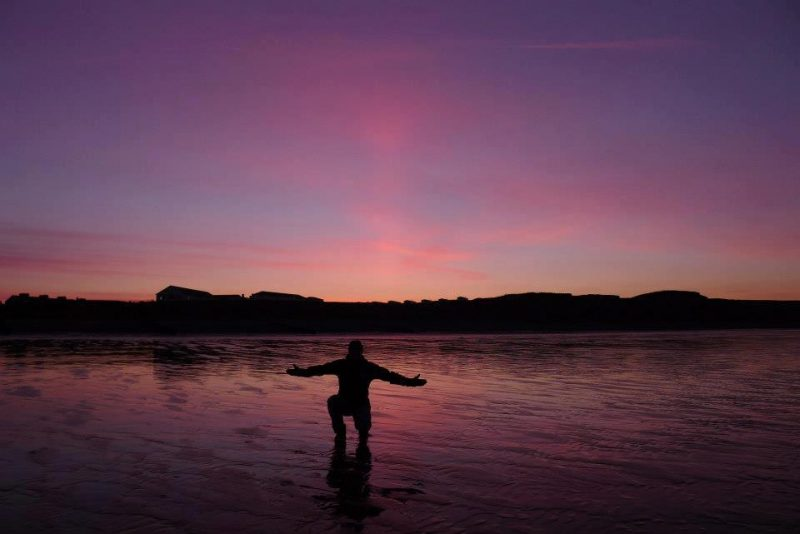 Easter morning sunrise, pink sky, man kneeling in water with arms held out.