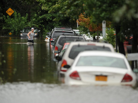 A man walks along cars on a flooded Croft Pl as Staten Island suffers flooding and damage by Hurricane Irene that pass through the New York City area.  Image Credit: Mark Bonifacio  New York Daily News