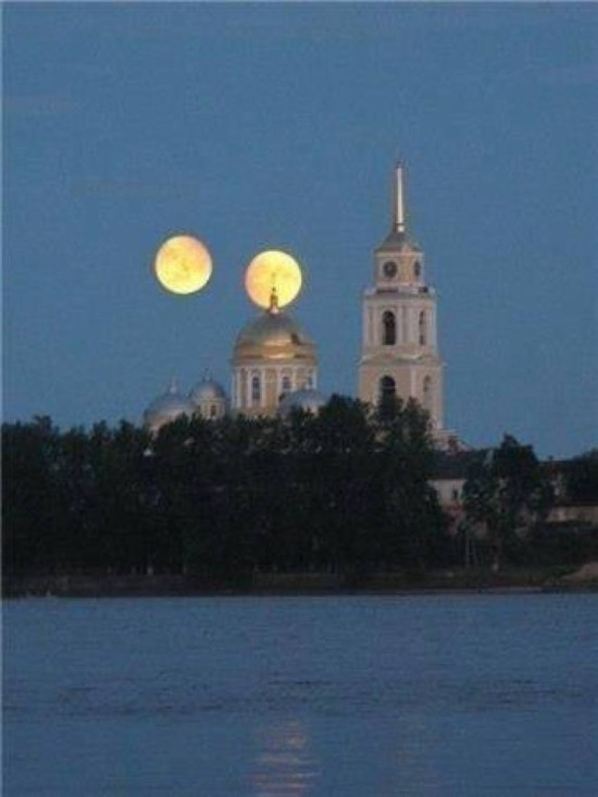 Two full moons side by side behind ancient church towers.