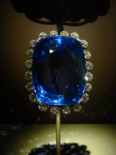 Large, dark blue, glittering faceted sapphire surrounded by small diamonds.