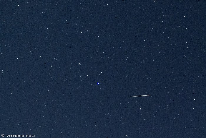 Thin horizontal white streak in star field with a large bright bluish star toward the center.