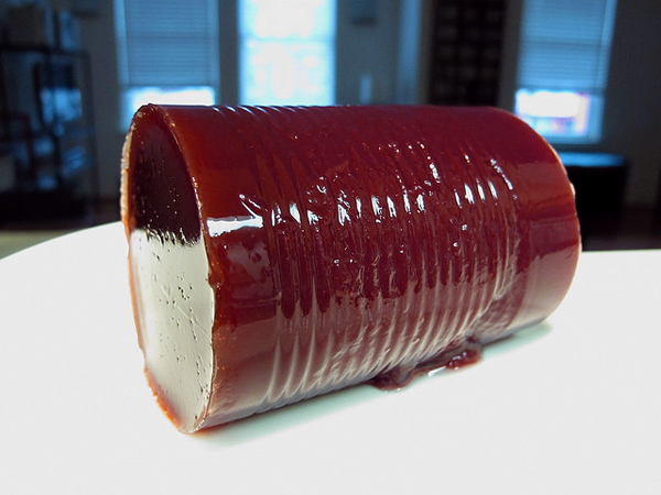 Shiny dark red ribbed cylinder lying on a plate.