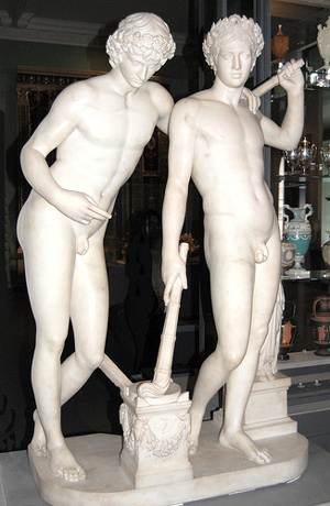 Marble statue of two naked, curly-haired, similar-looking youths standing next to each other.