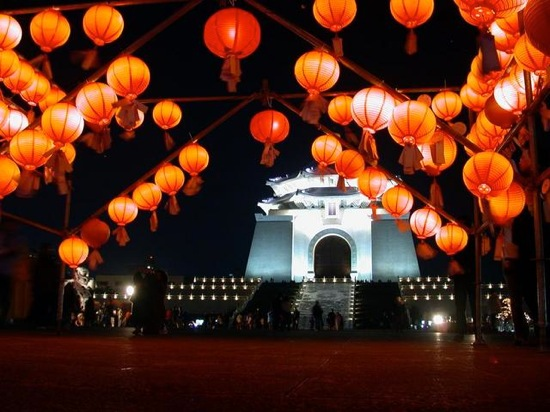Festoons of glowing Chinese lanterns in front of a lighted monument.