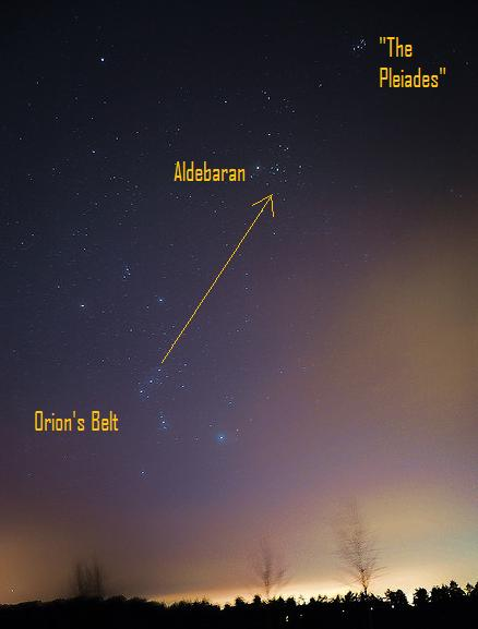 Starry sky with yellow arrow pointing from Orion belt stars to Pleiades.