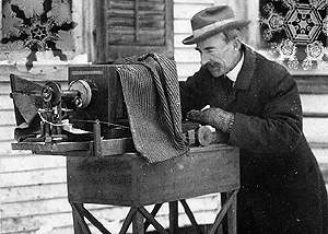 Man outside in the snow looking into old-fashioned camera apparatus.