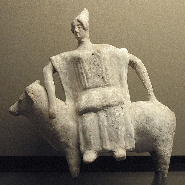 Crude figurine of woman sitting sideways on a bull.