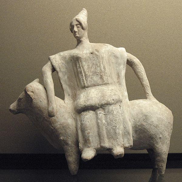 Crude figurine of woman sitting sideways on a bull.