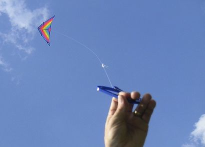 A hand, holding a kite string, with a triangular multicolor kite flying high overhead.