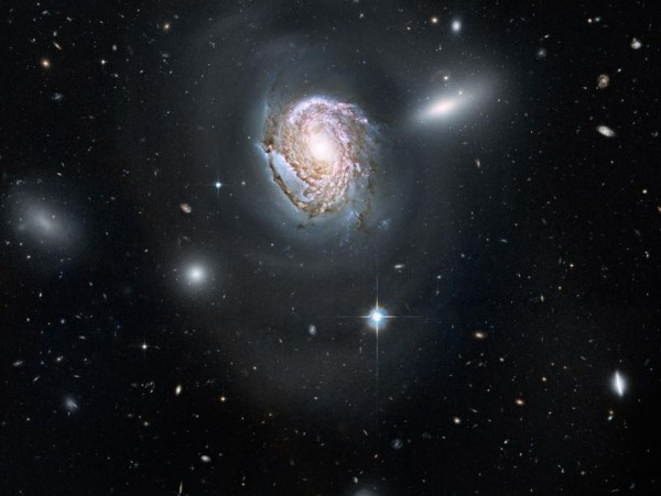 Large detailed spiral galaxy with smaller fuzzy oblong galaxies behind it.