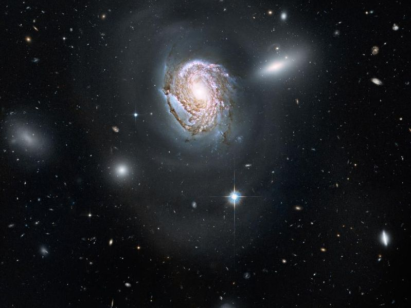 Large galaxy with smaller fuzzy galaxies behind it.