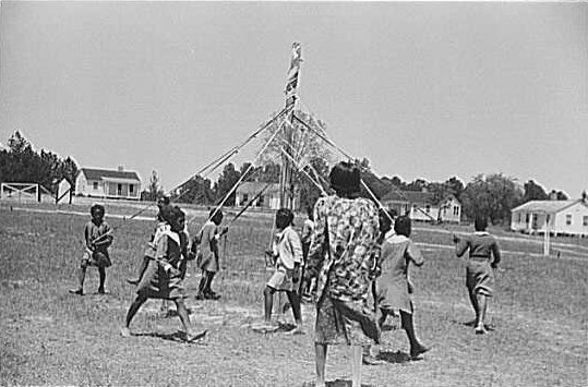 African-American children dancing around a pole holding ribbons tied to the top.