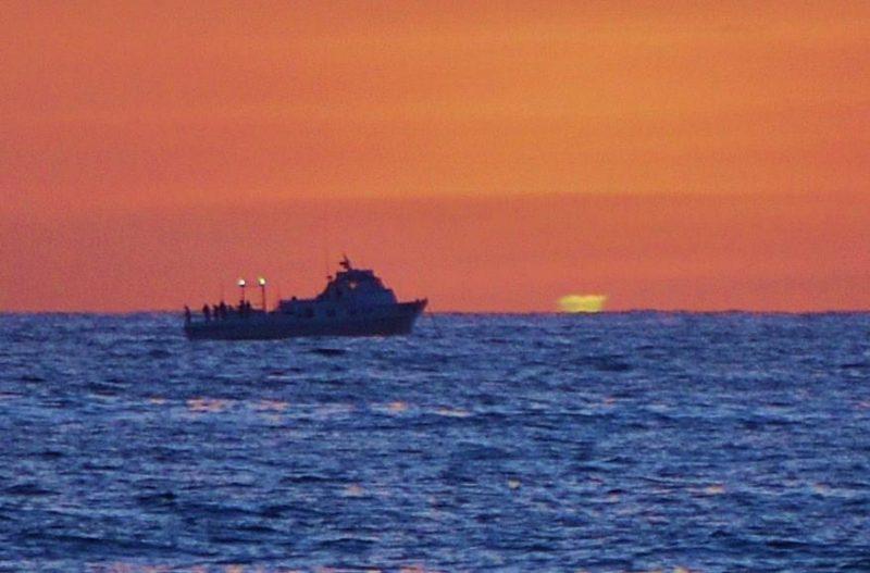Orange sky, blue sea, tugboat silhouette with green smudge on horizon.