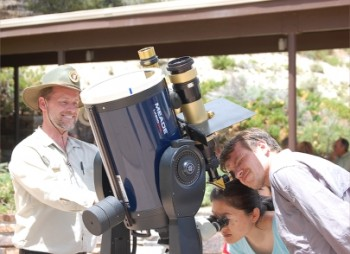 Daytime picture of people peering into the eyepiece of a filtered telescope.