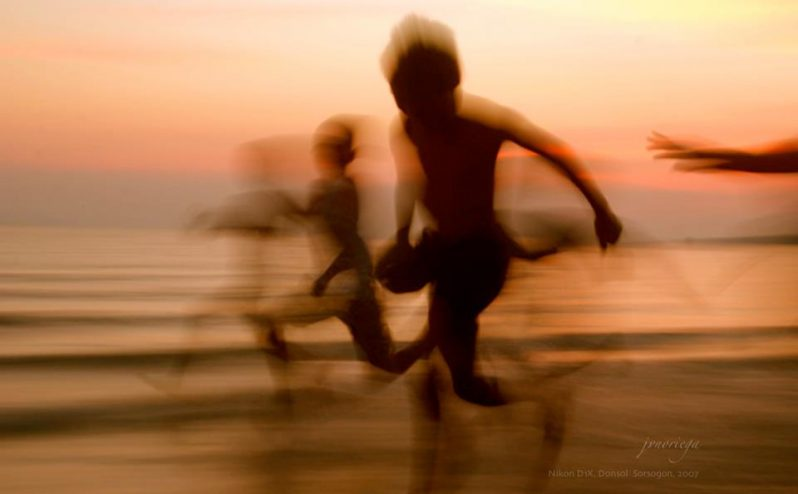 Blurred photo of running people on a beach.