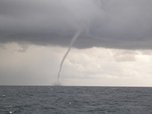 Long arcing funnel from low gray clouds to gray sea surface.