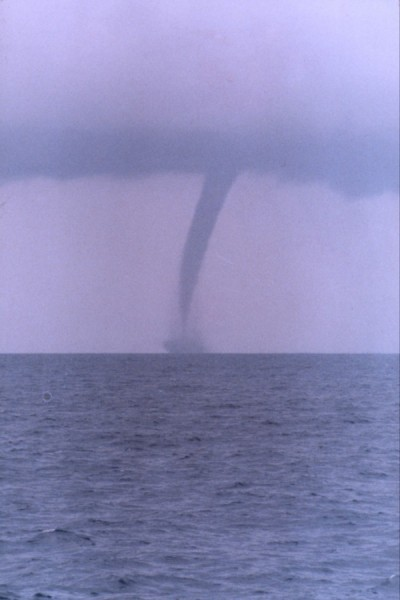 Long thin funnel from purple clouds to sea surface.
