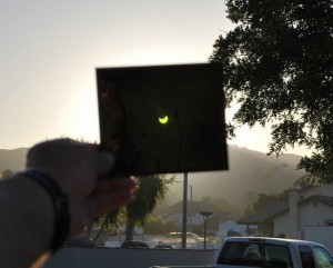 Large black square held up to the sun with a glowing crescent on it.