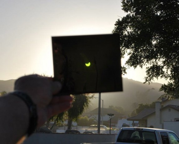 black square held up to the sun with an image of the partial eclipse on it