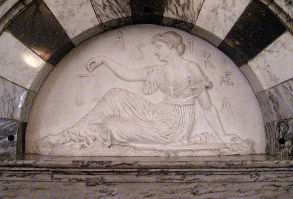 Relief scuplture of sitting woman in Greek garb holding a set of scales.