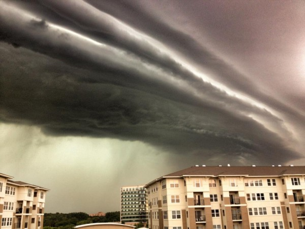 Dramatic image of clouds like long horizontal cylinders over a 3-story building.