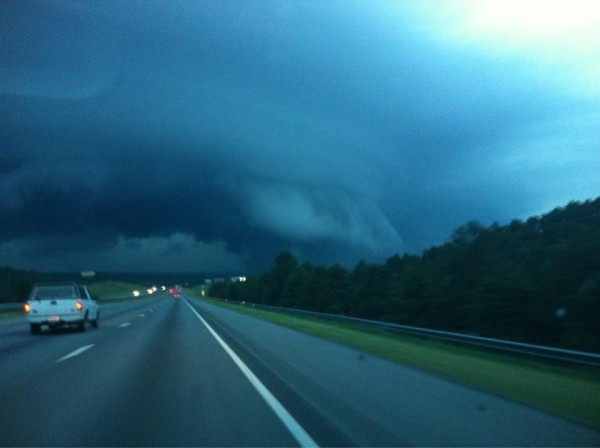 A shelf cloud, in blue-looking twilight, captured from a car moving along a highway.