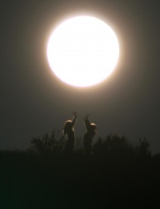Large bright full moon with two children standing in a field reaching toward it.