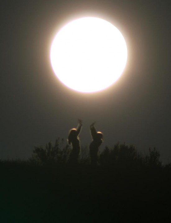 Two people standing facing each other reaching toward large overexposed full moon.