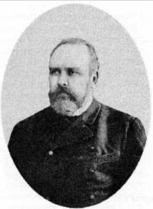A Victorian-era portrait of a bearded man in a dark suit.