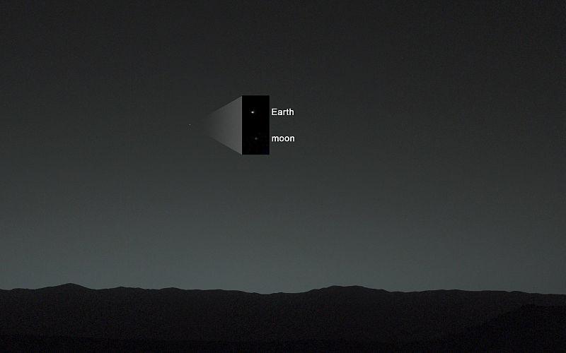 Ένα σκοτεινό τοπίο και πρασινωπός ουρανός με μια μικρή κουκκίδα και ένα εσωτερικό πλαίσιο που δείχνει δύο κουκκίδες πάνω στις οποίες γράφονται η γη και το φεγγάρι.