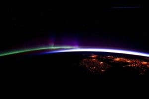 GLowing arcs of green, purple, and white light above scattered orange lights on dark surface.