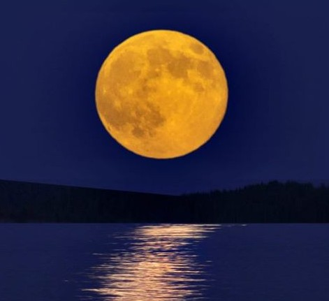 Large, brilliant yellow moon with its reflection in a lake.
