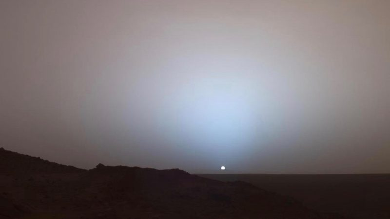 Sunset on Mars. Tiny sun with dark land in foreground.