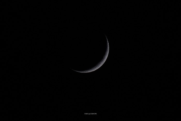 Very thin crescent moon against black sky.