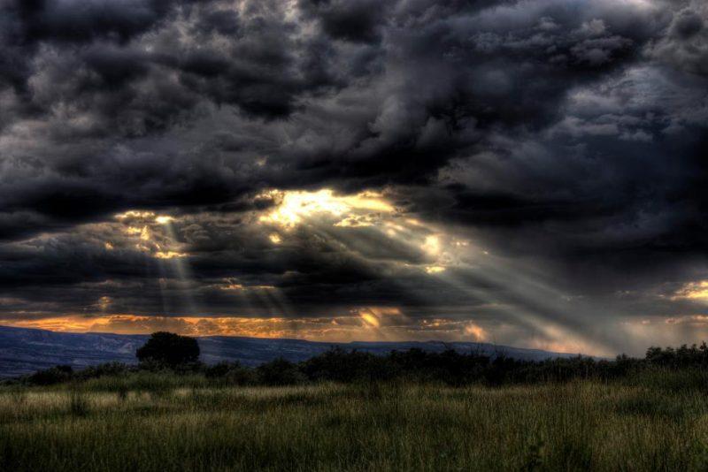 Sunlight coming through dark moody clouds over the Colorado range.