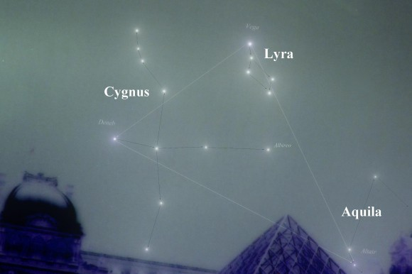 Triangle, plus stars of constellations Cygnus, Aquila, and Lyra above top of glass pyramid.